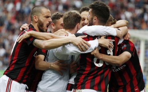 AC Milan's Nikola Kalinic, covered by his teammates, celebrates after scoring his side's third goal during the Serie A soccer match between AC Milan and Fiorentina at the San Siro stadium in Milan, Italy, Sunday, May 20, 2018. (AP Photo/Antonio Calanni)