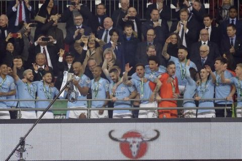 Manchester City players celebrate with the trophy after winning the English League Cup Final soccer match between Chelsea and Manchester City at Wembley stadium in London, England, Sunday, Feb. 24, 2019. (AP Photo/Tim Ireland)