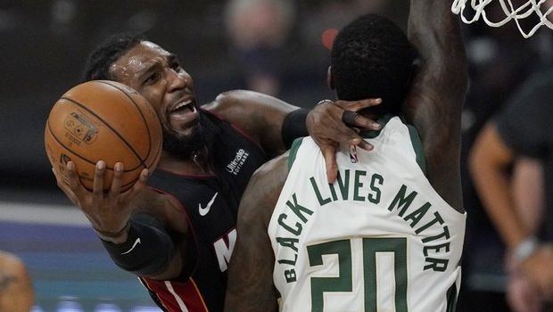 Miami Heat's Jae Crowder, left, goes to the basket defended by Milwaukee Bucks' Marvin Williams (20) in the first half of an NBA conference semifinal playoff basketball game Tuesday, Sept. 8, 2020 in Lake Buena Vista, Fla. (AP Photo/Mark J. Terrill)