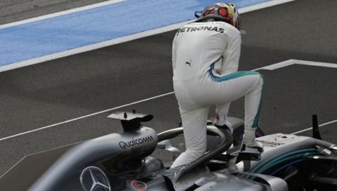 Mercedes driver Lewis Hamilton of Britain climbs out of his car after claiming pole position during qualifying practice at the Paul Ricard racetrack, in Le Castellet, southern France, Saturday, June 23, 2018. The Formula one race will be held on Sunday. (AP Photo/Claude Paris)
