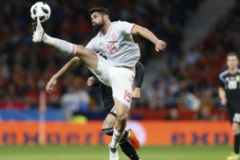 Spain's Diego Costa controls the ball before Argentina's Marcos Rojo, rear hidden, can intercept during the international friendly soccer match between Spain and Argentina at the Wanda Metropolitano stadium in Madrid, Spain, Tuesday, March 27, 2018. (AP Photo/Francisco Seco)