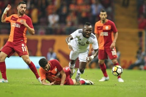 Ostersund's Samuel Mensah, center, is tackled during an UEFA Europa League second qualifying round, soccer match against Galatasaray, in Istanbul, Thursday, July 20, 2017.(AP Photo/Lefteris Pitarakis)