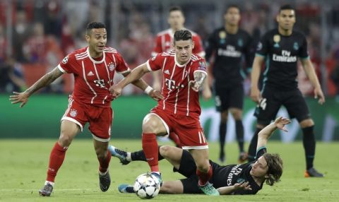 Real Madrid's Luka Modric, bottom right, looks to Bayern's Thiago, left, and Bayern's James, center, during the semifinal first leg soccer match between FC Bayern Munich and Real Madrid at the Allianz Arena stadium in Munich, Germany, Wednesday, April 25, 2018. (AP Photo/Matthias Schrader)