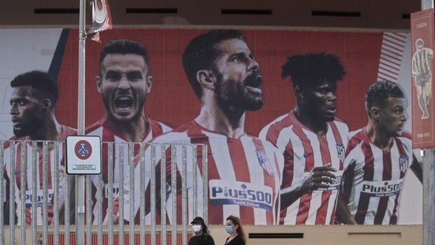 Two women wearing face masks pass by a giant poster of Atletico Madrid soccer players at the Wanda Metropolitano stadium in Madrid, Spain, Tuesday, May 5, 2020. The Spanish soccer league aims to restart in June without spectators. It's new compulsory protocols say all players, coaches and club employees must be tested for COVID-19 before training resumes, then regularly after that. All clubs' training facilities must be properly prepared and disinfected before players can start practising individually. (AP Photo/Paul White)