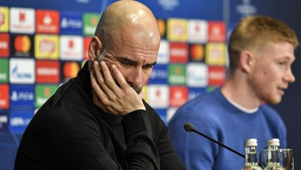 Manchester City manager Pep Guardiola looks down beside Kevin De Bruyne, right, during a press conference prior the Champions League round of 16, first leg, soccer match between FC Schalke 04 and Manchester City in Essen, Germany, Tuesday, Feb. 19, 2019. (AP Photo/Martin Meissner)