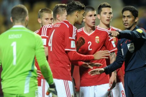 Saudi Arabia referee Fahad Al Mirdasi, right, is surrounded by player's from Hungary after awarding penalty to Brazil during their U20 soccer World Cup match in New Plymouth, New Zealand, Thursday, June 4, 2015. (AP Photo/Ross Setford)