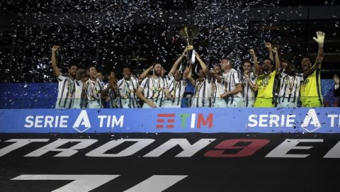 Juventus' Giorgio Chiellini and Juventus' Leonardo Bonucci hold up the trophy as Juventus players celebrate winning an unprecedented ninth consecutive Italian Serie A soccer title, at the end of the a Serie A soccer match between Juventus and Roma, at the Allianz stadium in Turin, Italy, Saturday, Aug.1, 2020. (AP Photo/Luca Bruno)