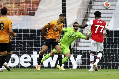 Arsenal's Bukayo Saka, right, scores the opening goal during the English Premier League soccer match between Wolverhampton Wanderers and Arsenal at the Molineux Stadium in Wolverhampton, England, Saturday, July 4, 2020. (Michael Steele/Pool via AP)