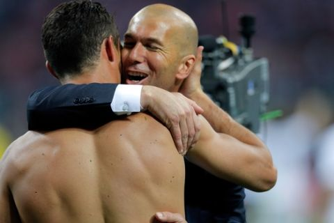 Real Madrid's Cristiano Ronaldo is embraced by Real Madrid's headcoach Zinedine Zidane after scoring the winning penalty shot during the Champions League final soccer match between Real Madrid and Atletico Madrid at the San Siro stadium in Milan, Italy, Saturday, May 28, 2016. Real Madrid won 5-4 on penalties after the match ended 1-1 after extra time.   (AP Photo/Manu Fernandez)