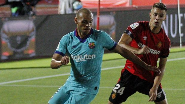 FC Barcelona's Martin Braithwaite, left, vies for the ball with Marllorca's Martin Valjent, right, during the Spanish La Liga soccer match between Mallorca and FC Barcelona at Son Moix Stadium in Palma de Mallorca, Spain, Saturday, June 13, 2020. With virtual crowds, daily matches and lots of testing for the coronavirus, soccer is coming back to Spain. The Spanish league resumes this week more than three months after it was suspended because of the COVID-19 pandemic. (AP Photo/Francisco Ubilla)