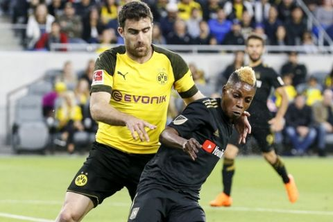Los Angeles FC forward Latif Blessing (7) of Ghana and Borussia Dortmund defender Sokratis Papastathopoulos (25) of Greece in actions during an international friendly soccer game between Los Angeles FC and Borussia Dortmund in Los Angeles, Tuesday, May 22, 2018. The game ended in a 1-1 draw. (AP Photo/Ringo H.W. Chiu)