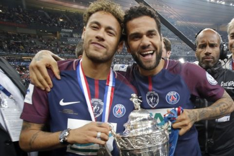 PSG's Neymar, left, and his teammate Dani Alves pose with the French Cup 2018 trophy at the Stade de France stadium in Saint-Denis, outside Paris, Tuesday, May 8, 2018. Paris Saint-Germain beat resilient third-division side Les Herbiers 2-0 to win the French Cup. (AP Photo/Michel Euler) PSG's Presnel Kimpembe