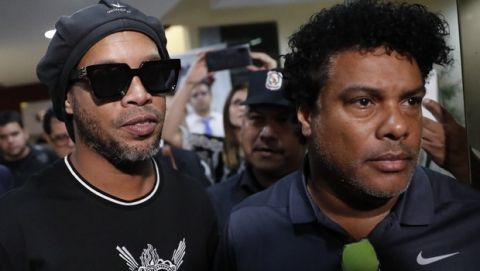 Former Brazilian soccer star Ronaldinho, whose full name is Ronaldo de Assis Moreira, center, and his brother Roberto, right, leave the attorney generals office after making a statement in Asuncion, Paraguay, Thursday, March 5, 2020. Ronaldinho and his brother were detained by Paraguayan police for allegedly entering the country with falsified passports on Wednesday. (AP Photo/Jorge Saenz)