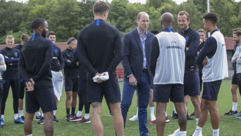 Britain's Prince William, centre right, talks to members of the England soccer team, during his visit to the FA training ground to meet players ahead of their friendly match against Costa Rica, in Leeds, England, Thursday, June 7, 2018. (Charlotte Graham/Pool Photo via AP)