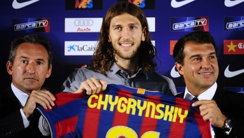Barcelona's new signing Ukranian Dmytro Chygrynskiy poses during his official presentation with Barcelona's president Joan Laporta, right, and Technical secretary Txiki Begiristain, left, in Barcelona, Spain, Monday, Aug. 31, 2009. (AP Photo/Manu Fernandez)