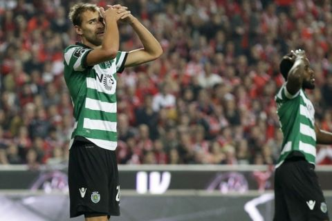 Sporting's Bas Dost, left, reacts after missing a chance to score during a Portuguese league soccer match between Benfica and Sporting at the Luz stadium in Lisbon, Sunday, Dec. 11, 2016. Benfica won 2-1. (AP Photo/Armando Franca)
