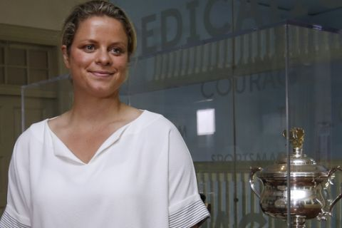 Belgian tennis star Kim Clijsters poses next to her 2011 Australian Open singles trophy displayed in the International Hall of Fame Tennis Museum, Friday, July 21, 2017, in Newport, R.I. Clijsters will be inducted into the Hall of Fame during enshrinement ceremonies on Saturday. (AP Photo/Elise Amendola)