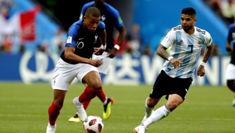 France's Kylian Mbappe, left, runs with the ball followed by Argentina's Ever Banega, right, during the round of 16 match between France and Argentina, at the 2018 soccer World Cup at the Kazan Arena in Kazan, Russia, Thursday, June 28, 2018. (AP Photo/Ricardo Mazalan)