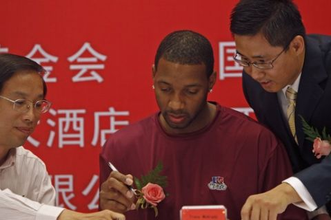 National Basketball Association's Houston Rockets player Tracy McGrady is aided by Chinese officials to sign on a document written in Chinese characters during a Chinese red cross event to benefit cancer patients in Beijing, China, Monday, Aug. 31, 2009.  (AP Photo/Elizabeth Dalziel)