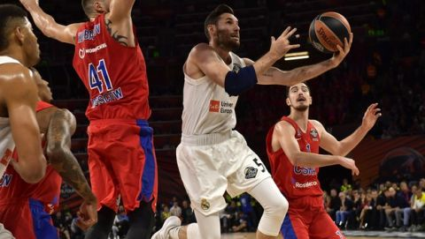 Madrid's Rudy Fernandez, second right, passes Moscow's Nikita Kurbanov, left, and Moscow's Nando De Colo, right, for a layup during the Euroleague Final Four semifinal basketball match between CSKA Moscow and Real Madrid at the Fernando Buesa Arena in Vitoria, Spain, Friday, May 17, 2019. (AP Photo/Alvaro Barrientos)