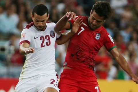 Qatars Ahmed Mohamed Elsayed, left, and Iran's Masoud Shojaei battle for the ball during the AFC Asia Cup soccer match between Qatar and Iran in Sydney, Australia, Thursday, Jan. 15, 2015. (AP Photo/Rick Rycroft)