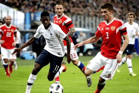 France's Ousmane Dembele, left, duels for the ball with Russia's Roman Neustadter during the international friendly soccer match between Russia and France at the Saint Petersburg stadium in St.Petersburg, Russia, Tuesday, March 27, 2018. (AP Photo/Dmitri Lovetsky)