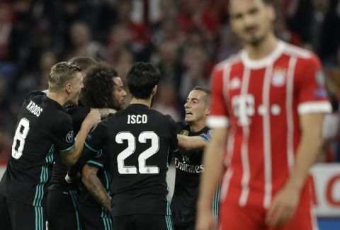 Real Madrid's Marcelo, second from left, is congratulated by his teammates after scoring their first goal during the semifinal first leg soccer match between FC Bayern Munich and Real Madrid at the Allianz Arena stadium in Munich, Germany, Wednesday, April 25, 2018. (AP Photo/Matthias Schrader)