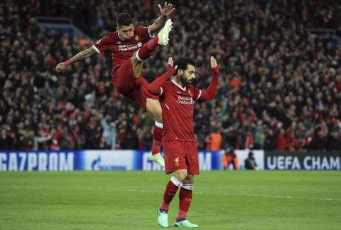 Liverpool's Mohamed Salah, right, celebrates scoring his side's second goal of the game with Roberto Firmino  against Roma during their Champions League, Semifinal first leg soccer match at Anfield, Liverpool, England, Tuesday April 24, 2018. (Peter Byrne/PA via AP)