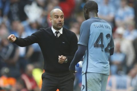 Manchester City manager Pep Guardiola, left, talks to Manchester City's Yaya Toure during the English FA Cup semifinal soccer match between Arsenal and Manchester City at Wembley stadium in London, Sunday, April 23, 2017. (AP Photo/Alastair Grant)