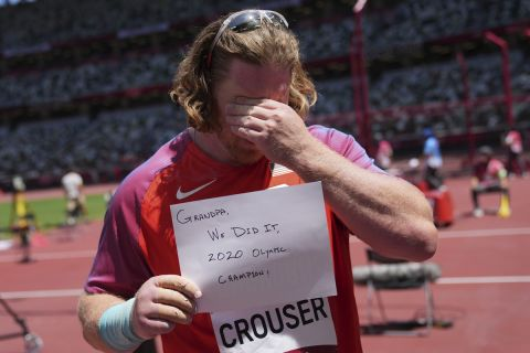 Ryan Crouser, of United States, holds up a sign after winning the final of the men's shot put at the 2020 Summer Olympics, Thursday, Aug. 5, 2021, in Tokyo. (AP Photo/Matthias Schrader)