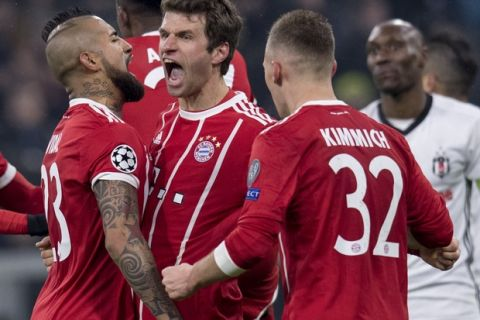 Bayern's Thomas Mueller is congratulated by his teammates Arturo Vidal, left, and  Joshua Kimmich, right, after scoring the opening goal during the Champions League round of 16 first leg soccer match between Bayern Munich and Besiktas Istanbul in Munich, southern Germany, Tuesday, Feb. 20, 2018.  (Sven Hoppe/dpa via AP)