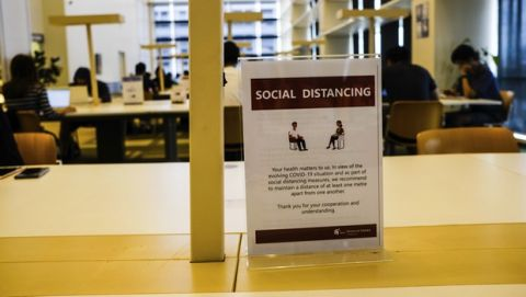In this March 16, 2020, photo, a sign about social distancing is placed on a table at the National Library in Singapore. As the virus outbreak spreads ever further, it's becoming clear that some strategies are more likely to succeed in containing it: pro-active efforts to track down and isolate cases, access to basic, affordable public health and clear, reassuring messaging from leaders. (AP Photo/Ee Ming Toh)