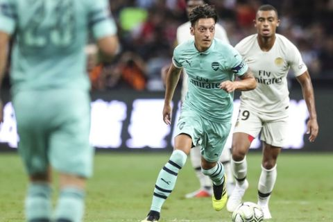 Arsenal's Mesut Ozil, center, controls the ball during the International Champions Cup match between Arsenal and Paris Saint-Germain in Singapore, Saturday, July 28, 2018. (AP Photo/Yong Teck Lim)