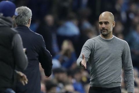 Manchester City coach Pep Guardiola, right, shakes hands with Manchester United manager Jose Mourinho at the end of the English Premier League soccer match between Manchester City and Manchester United at the Etihad Stadium in Manchester, England, Saturday April 7, 2018. (AP Photo/Matt Dunham)
