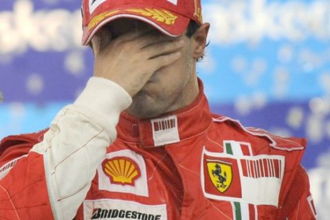 ** FILE ** This Nov. 2, 2008, file photo shows Ferrari's Formula One driver Felipe Massa of Brazil covering his face after he won the Brazilian Grand Prix but failed to secure the 2008 Formula One drivers championship title on the Interlagos circuit in Sao Paulo, Brazil. Governing body FIA says that Formula One's championship will be decided by the number of race wins and not accumulated points. Under the new system, Ferrari's Felipe Massa would have won the 2008 championship instead of Lewis Hamilton of McLaren. The Brazilian driver won six grand prix races to Hamilton's five last year. (AP Photo/Oliver Multhaup, File)