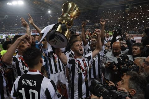 Juventus' Miralem Pjanic holds up the trophy as he celebrates with teammates after beating AC Milan 4-0 in the Italian Cup final soccer match, at the Rome Olympic stadium, Wednesday, May 9, 2018. (AP Photo/Gregorio Borgia)
