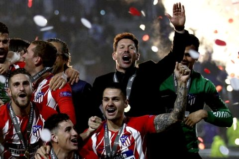 Atletico's head coach Diego Simeone, in black suit, celebrates with his players after winning the Europa League Final soccer match between Marseille and Atletico Madrid at the Stade de Lyon in Decines, outside Lyon, France, Wednesday, May 16, 2018. (AP Photo/Francois Mori)