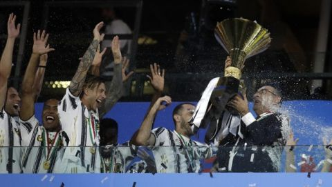 Juventus' head coach Maurizio Sarri, right, holds up the trophy while Juventus players celebrate winning an unprecedented ninth consecutive Italian Serie A soccer title, at the end of the a Serie A soccer match between Juventus and Roma, at the Allianz stadium in Turin, Italy, Saturday, Aug.1, 2020. (AP Photo/Luca Bruno)