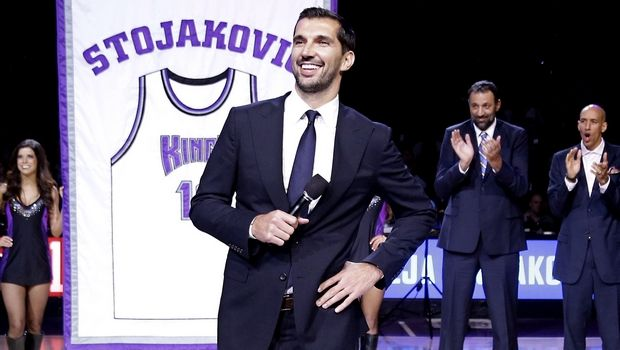 Former Sacramento Kings forward Peja Stojakovic, of Serbia, smiles after the team retired his jersey during a ceremony at the half time of an NBA basketball game against the Oklahoma City Thunder  in Sacramento, Calif., Tuesday, Dec. 16, 2014.  In the background are Stojakovic's former Kings teammates Vlade Divac, third from right, of Serbia,  Doug Christie, second from right, and Scott Pollard, right, The Thunder won 104-92. (AP Photo/Rich Pedroncelli)