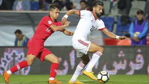 Turkey's Cengiz Under, left, tries to stop Iran's Ramin Rezaeian, right, during a friendly soccer match between Turkey and Iran, in Istanbul, Monday, May 28, 2018. (AP Photo)