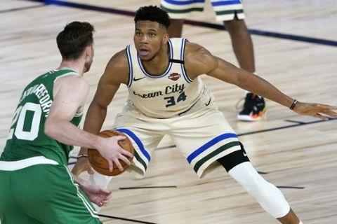 Boston Celtics' Gordon Hayward (20) looks to pass as Milwaukee Bucks' Giannis Antetokounmpo (34) defends during the second half of an NBA basketball game Friday, July 31, 2020, in Lake Buena Vista, Fla. (AP Photo/Ashley Landis, Pool)