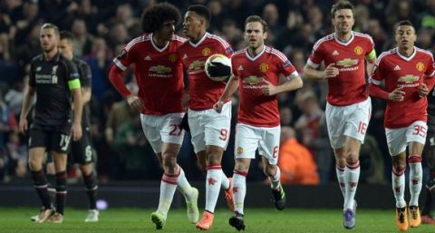 """""""Manchester United's French striker Anthony Martial (C) carries the ball back to the centre circle after scoring the opening goal during the UEFA Europa League round of 16, second leg football match between Manchester United and Liverpool at Old Trafford in Manchester, north west England on March 17, 2016. / AFP / OLI SCARFF        (Photo credit should read OLI SCARFF/AFP/Getty Images)"""""""