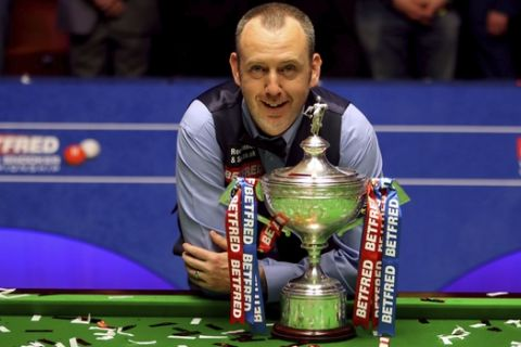 Britain's Mark Williams poses with the trophy after winning the 2018 Snooker World Championship at The Crucible, Sheffield, England, Monday, May 7, 2018. Mark Williams has won the world snooker championship for the third time, 15 years after his last, after beating John Higgins 18-16 in one of the great finals at the Crucible Theatre. At 43, Williams became the oldest winner of the sports biggest prize since fellow Welshman Roy Reardon won his sixth and final world title in 1978. (Richard Sellers/PA via AP)