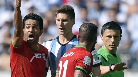 Iran's Masoud Shojaei and Ashkan Dejagah (21) argue with referee Milorad Mazic from Serbia during the group F World Cup soccer match between Argentina and Iran at the Mineirao Stadium in Belo Horizonte, Brazil, Saturday, June 21, 2014. (AP Photo/Martin Meissner)