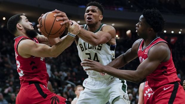 Milwaukee Bucks' Giannis Antetokounmpo is fouled as he drives between Toronto Raptors' Fred VanVleet and OG Anunoby during the second half of an NBA basketball game Saturday, Nov. 2, 2019, in Milwaukee. The Bucks won 115-105. (AP Photo/Morry Gash)