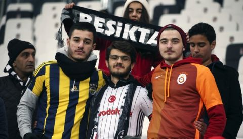 Supporters wearing jerseys of the three major Turkish soccer teams, from left, Fenerbahce, Besiktas and Galatasaray, pose together inside the Besiktas Vodafone Arena stadium, prior to a Turkish Cup soccer match between Beisktas and Kayserispor, the first soccer match since Saturday's twin attacks outside and near the stadium, in Istanbul, Wednesday, Dec. 14, 2016. Turkish authorities have banned distribution of images relating to the Istanbul explosions within Turkey. (AP Photo)