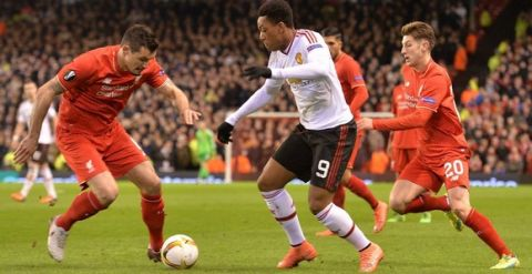 """""""Manchester United's French striker Anthony Martial (C) vies with Liverpool's English midfielder Adam Lallana (R) during the UEFA Europa League round of 16, first leg football match between Liverpool and Manchester United at Anfield in Liverpool, northwest England on March 10, 2016. / AFP / PAUL ELLIS        (Photo credit should read PAUL ELLIS/AFP/Getty Images)"""""""