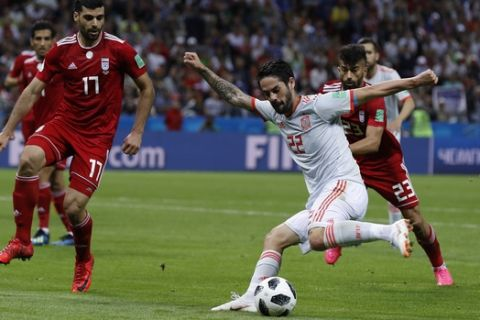 Spain's Isco, front, is challenged by Iran's Mehdi Taremi, left, during the group B match between Iran and Spain at the 2018 soccer World Cup in the Kazan Arena in Kazan, Russia, Wednesday, June 20, 2018. (AP Photo/Manu Fernandez)