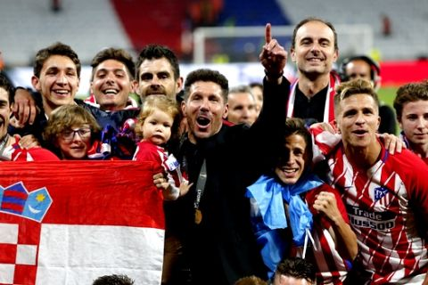 Atletico's head coach Diego Simeone, in black suit, celebrates with his players after winning the Europa League Final soccer match between Marseille and Atletico Madrid at the Stade de Lyon in Decines, outside Lyon, France, Wednesday, May 16, 2018. (AP Photo/Thibault Camus)