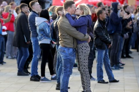 A couple kiss during the opening match of the 2018 soccer World Cup, between Russia and Saudi Arabia, in the fan zone in Yekaterinburg, Russia, Thursday, June 14, 2018. (AP Photo/Vadim Ghirda)